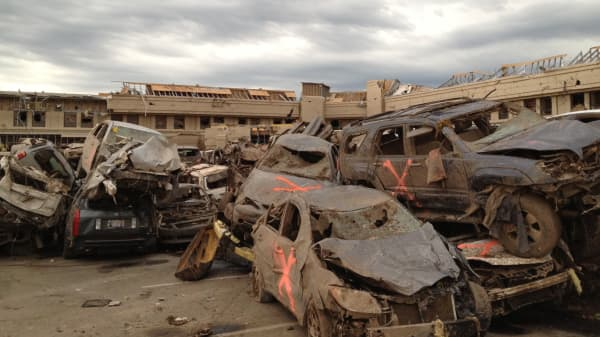 Cars are piled up after a devastating tornado hits Moore, Oklahoma are marked with with spray paint after they were searched for victims.